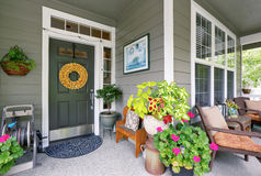 Cozy entrance porch with flower pots and seating arrangement Stock Photography