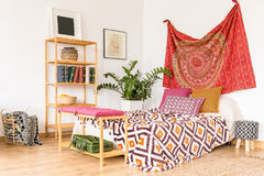 Cozy ethnic bedroom. With wooden book-stand and oriental cloth stock images