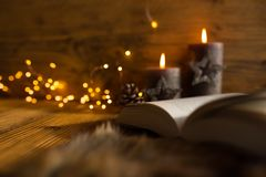 Cozy evening with christmas lights and book stock images