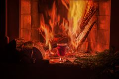 A cozy evening by the fireplace with mulled wine. Burning fire, warm cozy atmosphere, dark photo stock images