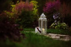 Cozy evening garden scene with vintage lantern and candle holder Royalty Free Stock Images