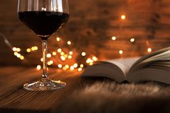 Cozy evening with wine and a good book. Glass of red wine with a good book and gold bokeh on a cozy winter evening royalty free stock images