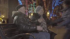 Cozy family evening park grandson little boy running over to grandparent hugging in festive christmas illumination light stock video