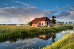 Cozy farmhouse in gold sunset sunlight Stock Photography