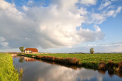Cozy farmhouse by river in morning light Royalty Free Stock Photos