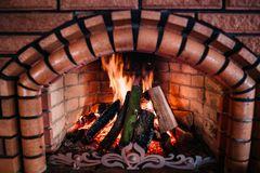 Cozy fire in a stone fireplace. Cozy flaming fire in a stone fireplace with red lights royalty free stock photos
