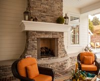 Cozy fireplace relaxation. A beautiful outdoor covered fireplace is ready for relaxation at this executive luxury retreat Stock Photos