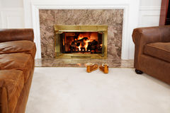 Cozy fireside and slippers Royalty Free Stock Photos