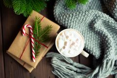 Cozy flat lay. Gifts wrapped with craft paper, decorated with candy cane and cup mug of coffee cacao on a rustic dark royalty free stock image