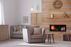 Cozy furnished apartment with niche in wooden wall and armchair. Interior design royalty free stock photography
