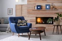Cozy furnished apartment with niche in wooden wall and armchair. Interior design royalty free stock photo