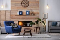 Cozy furnished apartment with niche in wooden wall. And armchair. Interior design royalty free stock image