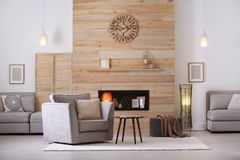 Cozy furnished apartment with niche. In wooden wall and armchair. Interior design stock photo
