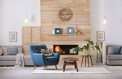 Cozy furnished apartment with niche in wooden wall and armchair. Interior design stock image
