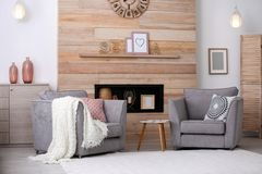 Cozy furnished apartment with niche in wooden wall. And armchair. Interior design stock photos