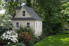 Cozy Garden House. A charming playhouse cottage sits at the edge of a shaded perennial garden stock image