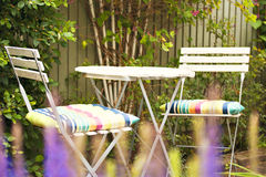 Cozy garden seating area. Image of cozy seating area in lush garden Royalty Free Stock Images