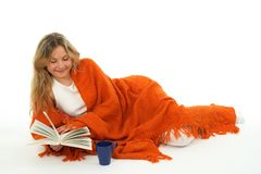 Cozy girl reading a book, smiling Stock Photos