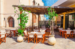 Cozy Greek restaurant in shade with wooden chairs Royalty Free Stock Photography