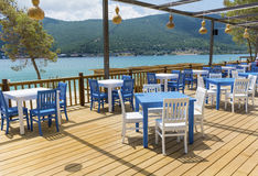 Cozy greek  restaurant with white chairs and blue tables Stock Photos