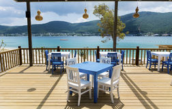 Cozy greek  restaurant with white chairs and blue tables Royalty Free Stock Images