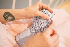Cozy handmade knitting crochet process. Woman hands holding tools. Royalty Free Stock Photography