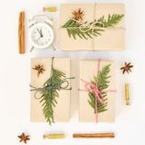 Cozy holiday white background. Christmas composition of spruce branches, gift, alarm clock, cinnamon, anise and confetti in small stock image