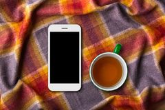 Cozy home atmosphere. Modern mobile phone with blank screen and cup of tea on bedclothes. Spending weekend under warm coverlet wit Royalty Free Stock Photography