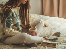 Cozy home. Beautiful girl is reading a book on the bed. Good morning with tea. Pretty young girl relaxing. The concept of reading royalty free stock images