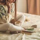 Cozy home. Beautiful girl is reading a book on the bed. Good morning with tea. Pretty young girl relaxing. The concept of reading stock photos
