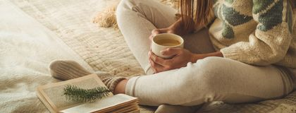 Cozy home. Beautiful girl is reading a book on the bed. Good morning with tea. Pretty young girl relaxing. The concept of reading royalty free stock photography