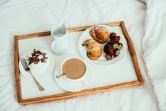 Cozy home breakfast in bed in white bedroom interior. With new linen bedding stock image