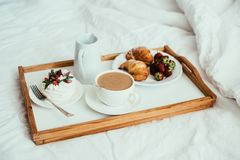 Cozy home breakfast in bed in white bedroom interior. With new linen bedding royalty free stock photography