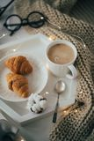 Cozy home breakfast, warm blanket, coffee and croissant on white Royalty Free Stock Photography