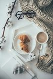 Cozy home breakfast, warm blanket, coffee and croissant on white Stock Photography