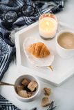 Cozy home breakfast, warm blanket, coffee and croissant on white Stock Photos