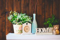 Cozy home interior, clock, vase with flowers, toy bear Stock Photography