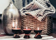 Cozy home interior decor, burning candles on a multi-colored rug on the background of a metal vase.  royalty free stock image