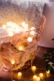 Home interior decoration, metal basket with pillow, warm blanket. Cozy home interior decoration, metal basket with pillow, warm blanket and string lights on the Royalty Free Stock Image