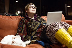 Cozy Home Interior pensive Woman using Computer playing with Cat Royalty Free Stock Photography