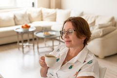 Cozy home morning. Woman drinking coffee with milk. Cozy home morning. Middle age woman in beige color home interior drinking coffee with milk Stock Image