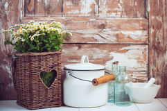 Cozy home rustic decor. Flowers in a wicker basket, glass bottles and vintage milk can on wooden background, cozy home rustic decor, cottage living Royalty Free Stock Photo