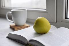Cozy home still life: cup of hot coffee and opened book with green apple on windowsill against snow landscape outside Stock Photo
