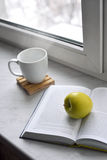 Cozy home still life: cup of hot coffee and opened book with green apple on windowsill against snow landscape outside Royalty Free Stock Photos