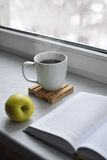 Cozy home still life: cup of hot coffee and opened book with green apple on windowsill against snow landscape outside Royalty Free Stock Images