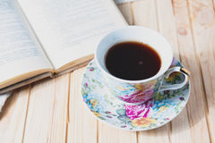 Cozy home still life: cup of hot coffee or tea and opened book Royalty Free Stock Photos