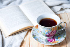 Cozy home still life: cup of hot coffee or tea and opened book with warm plaid Royalty Free Stock Images