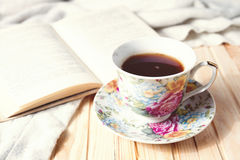 Cozy home still life: cup of hot coffee or tea and opened book with warm plaid Stock Photography