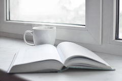Cozy home still life: cup of hot coffee or tea and opened book on windowsill. Education concept, free copy space Stock Photos