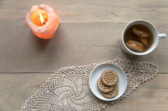 Cozy home still life.Top view. Cozy home still life. Candle of pink salt with fire, a cup of apple compote and plate with cookies on knitted napkin on a light Royalty Free Stock Photo